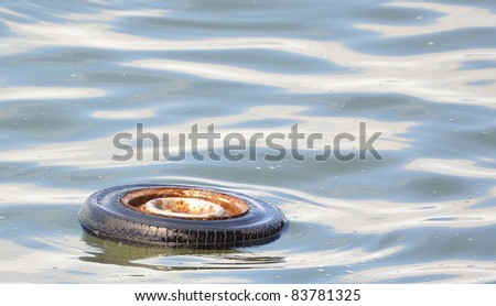 An old car tire in a lake - stock photo