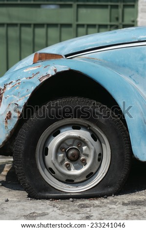 An old car with a flat tire - stock photo