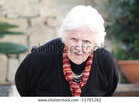 an old caucasian woman bending down showing a hunched back