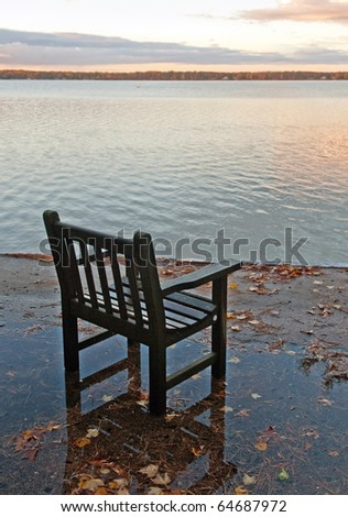 an old chair overlooking a scenic lake in the morning - stock photo