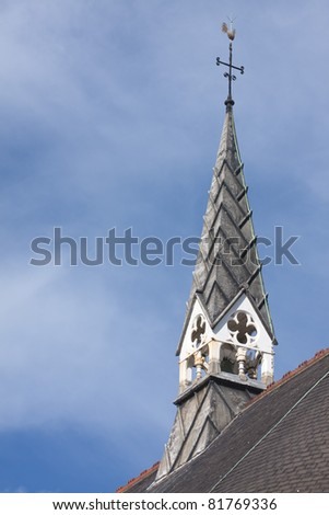 An old church spire set against a bright blue sky