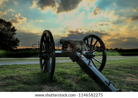 an old Civil War cannon points towards the sunset at Stones River National Battlefield in Murfreesbore Tennessee