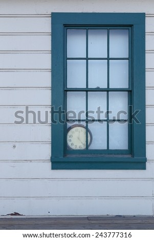 An old clock lies forgotten behind a window.