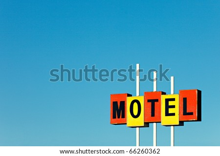 An old commercial motel sign against a clear blue sky. - stock photo