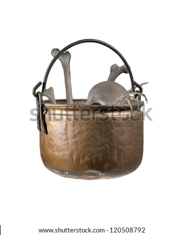 An old copper witches cauldron filled with human bones - stock photo