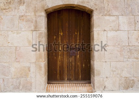 An old dark brown wooden castle door in the Castell de Montjuïc (Barcelona, Spain), with metal door opener and antique keyhole, surrounded by stone wall - stock photo