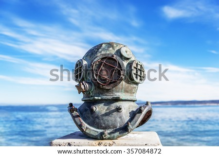 An old deep sea diving helmet, near Cannery Row in Monterey, California (USA) commemorates the divers and who installed and maintained underwater sardine pipes and pumps, including 2 who died. - stock photo
