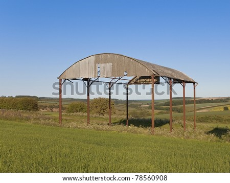 an old derelict barn on a hillside in the middle of an agricultural landscape - stock photo