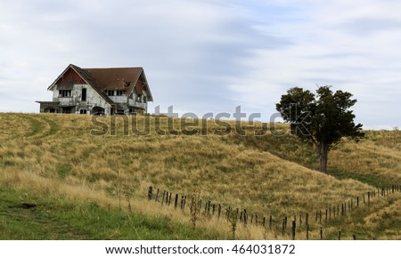An old dilapidated house sits atop a hill with a single tree in the field below behind a fence that is equally aged.