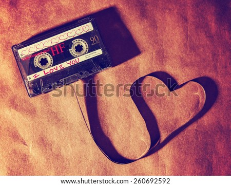 an old dirty grungy scratched up audio cassette tape in the shape of heart (focus on the words) on a brown paper texture background good for valentine's day or love greeting cards (SHALLOW DOF) - stock photo