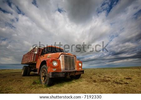 An old farm truck against a dramatic prairie landscape - stock photo
