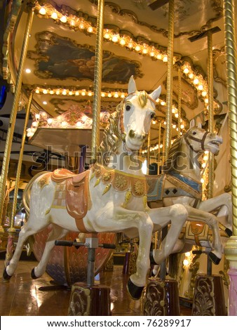 An old fashioned carousel at night. Detail of two horses - stock photo