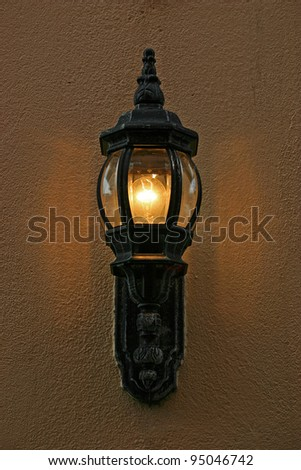 An old fashioned lamppost on a stucco wall - stock photo