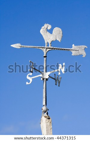 An old fashioned steel weather vane isolated against a bright blue sky - stock photo