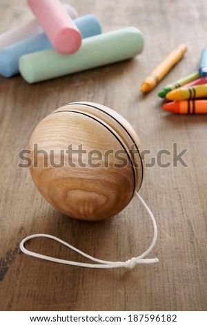 An old fashioned wooden yo yo with chalks and wax crayons a retro childhood concept - stock photo