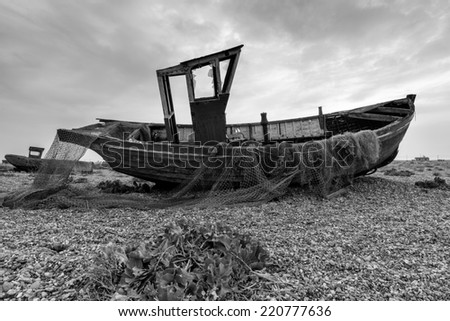 An old fishing boat with nets in black and white