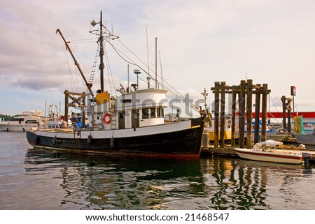 An old fishing trawler docked at a pier - stock photo