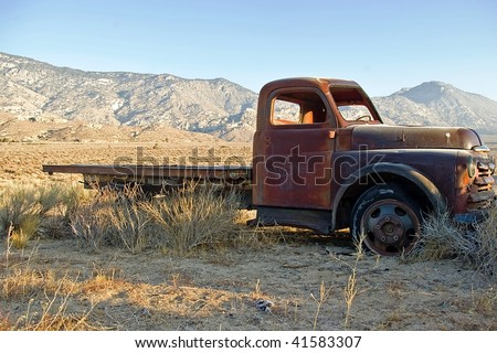 An old flatbed truck in a high desert valley. - stock photo