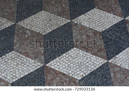An old floor pattern with dark tiles forming a three dimensional diamond pattern.