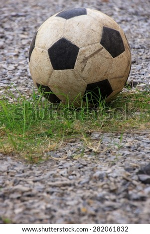 An old football or soccer ball on crushed gravel yard. - stock photo