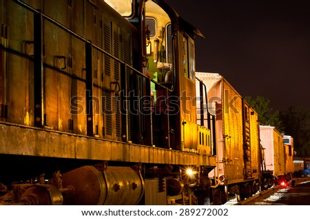 An old freight train reflects golden light at dusk - stock photo