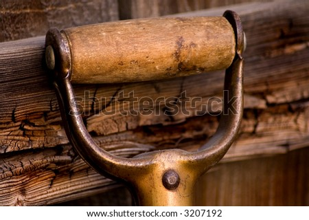An old garden shovel handle. - stock photo