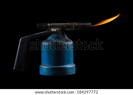 An Old Gas Burner with Flame Isolated on a Black Background - stock photo