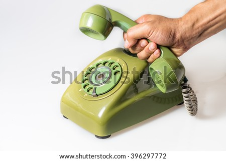 an old green rotary phone on white with clipping path