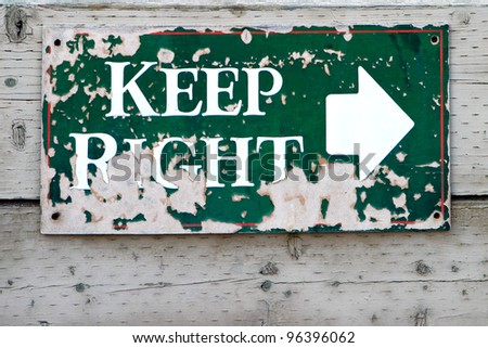 """An old green sign with peeling paint reading """"Keep Right,"""" mounted on an old wooden wall. - stock photo"""