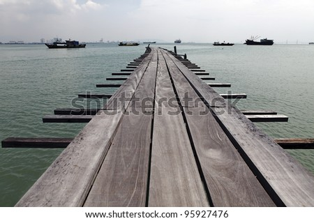 An old grungy timber jetty extending into the sea with passing ships, on the Tan Jetty, which is a UNESCO heritage site, in Penang, Malaysia. - stock photo