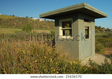 An old guard shack sits among weeds at an abandoned military site.