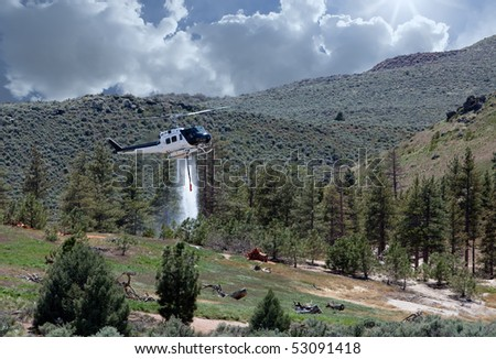 An old helicopter converted from military use to civilian fire fighting by the addition of a 360 gallon water drop tank and siphon dropping a water/fire retardant mixture during a practice exercise. - stock photo