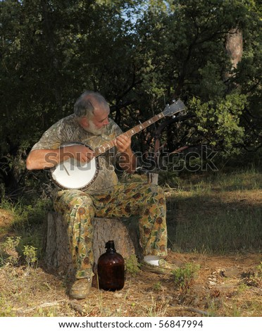 An old hillbilly banjo player with his moonshine jug playing an Appalachian folk song. - stock photo