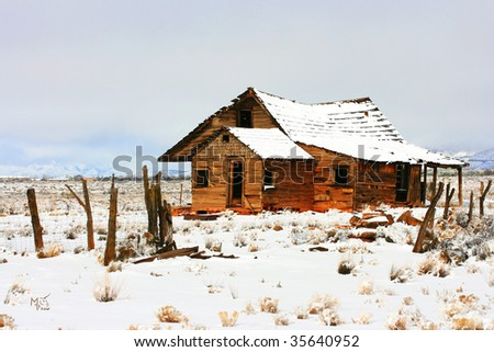 an old homestead on a prairie in the middle of nowhere after a snowstorm - stock photo
