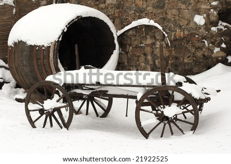 an old horse drawn carriage in the snow - stock photo