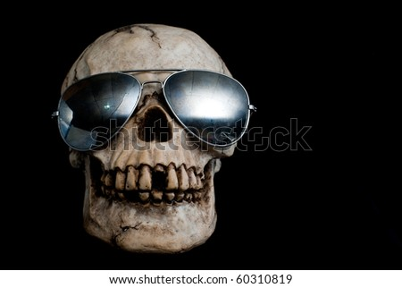 An old, human skull wearing mirrored aviator type sunglasses. - stock photo