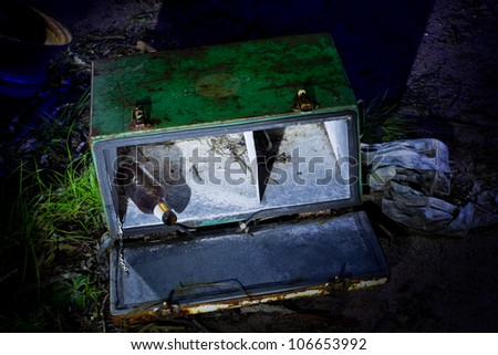 An old ice box with beer bottle falling out lightpainted at night - stock photo