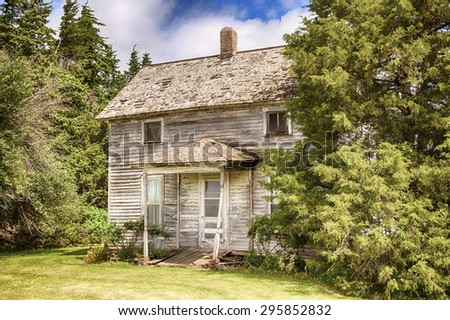 An old Iowa farmhouse is slowly decaying although the lawn and landscaping are being maintained. - stock photo