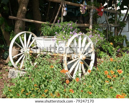 An old iron cart overflowing with  colorful flowers