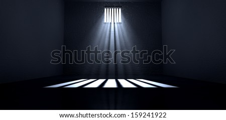 An old jail cell interior with barred up window with light rays penetrating through it reflecting the image on the floor - stock photo