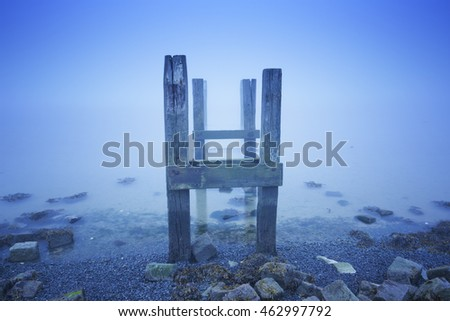 An old jetty in the sea on the island of Terschelling in The Netherlands. Photographed on a foggy morning at dawn.