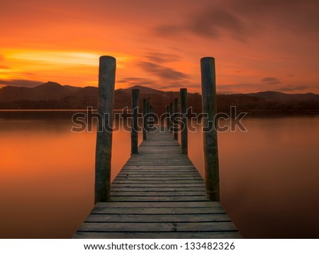 An old jetty on the still water of Derwent Water in Cumbria with lovely sun set - stock photo