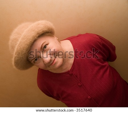 An old lady in hat with roguish smile look up