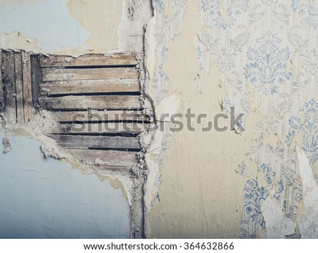 An old lath and plaster wall with antique wallpaper - stock photo