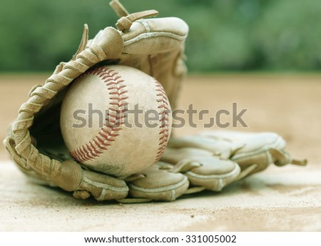 An old leather baseball mitt, or glove with a worn baseball laying on a home plate. There is clay around. Home plate needs to be dusted off. Vintage filter applied. Shallow depth of field. - stock photo