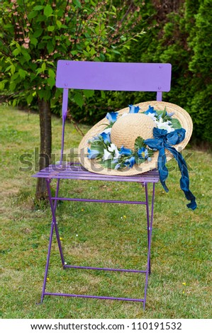 An old lilac folding chair with a broad-brimmed straw hat. On the hat there are some flowers.