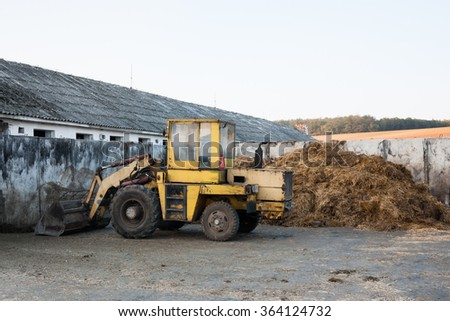 An old loader and pile of cow manure on the farm