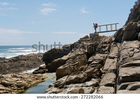 An old male backpacker looks at sea. Shot on the Otter trail in the Tsitsikamma National Park, Garden Route area, Western Cape, South Africa.  - stock photo