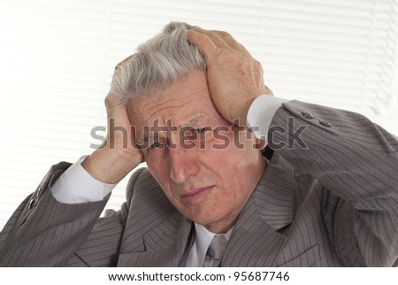 an old man holding his head on a light background