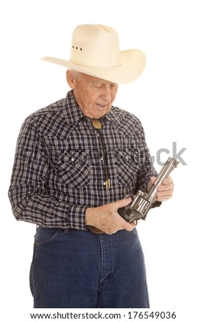 An old man in a cowboy hat holding a pistol in his hands. - stock photo
